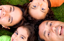 Close up of a family of four laying down in the grass with their heads together all smiling